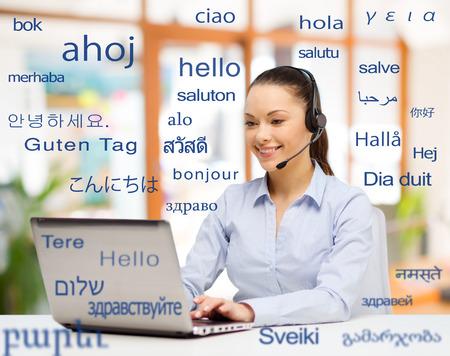 Concepto de traducción, negocios y tecnología: traductora u operadora sonriente con computadora en la oficina sobre palabras de saludo en diferentes idiomas extranjeros