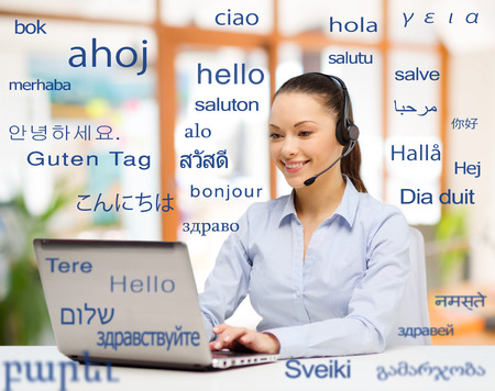 translation, business and technology concept - smiling female translator or operator with computer at office over greeting words in different foreign languages