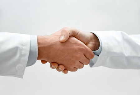 close up of two male doctors shaking hands