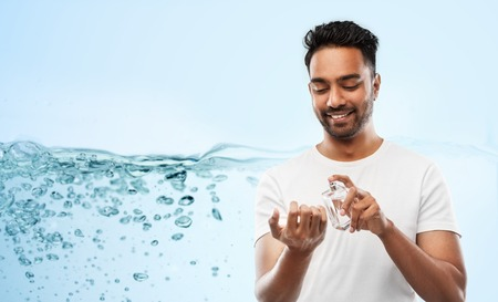 happy indian man with perfume over blue background Stock Photo