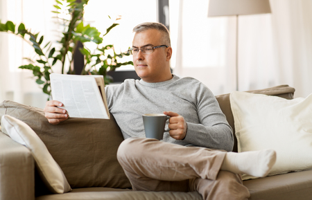 man reading newspaper and drinking coffee at home
