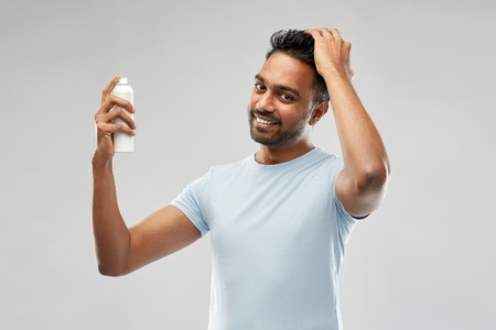 Sonriente hombre indio aplicando spray para el cabello sobre gris