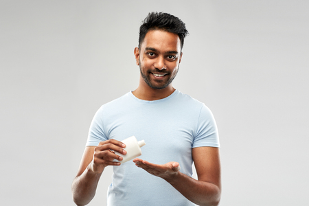 happy indian man applying lotion to his hand Stock Photo