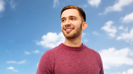 smiling young man over blue sky background 스톡 콘텐츠