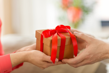 close up of male and female hands with gift box