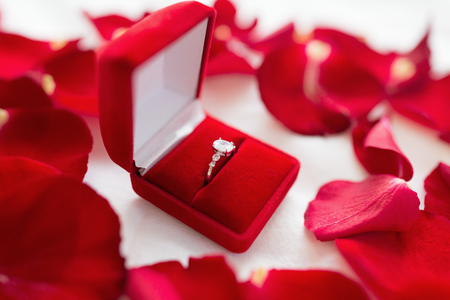 diamond ring in red velvet gift box on bed sheet