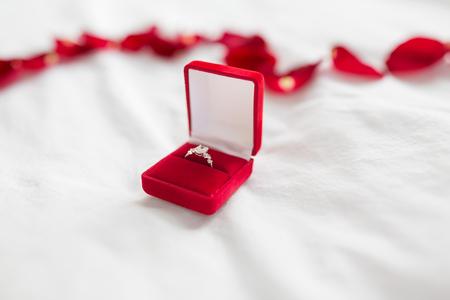 bague en diamant dans une boîte cadeau en velours rouge sur un drap de lit