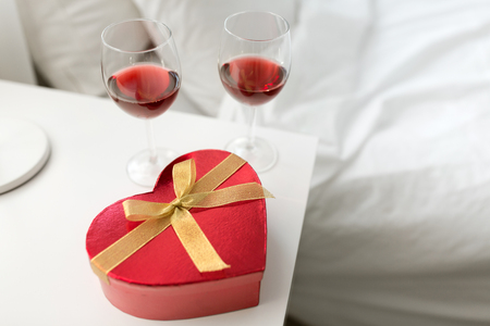 gift and two glasses of wine in bedroom at home