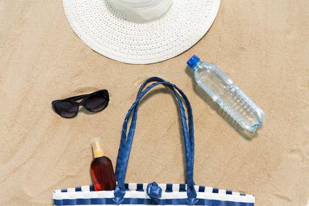 beach bag, sunscreen, sunglasses and hat on sand