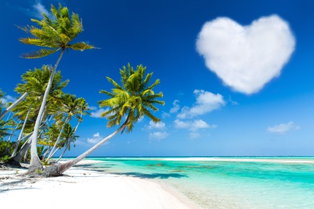 romantic beach with palms and heart shaped cloud