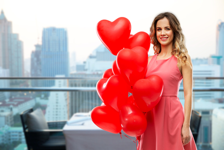 woman with red heart shaped balloons in singapore Standard-Bild