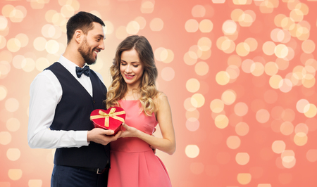 valentines day and people concept - happy couple with gist box in shape of heart over living coral background and festive lights