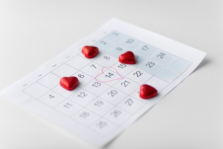 close up of calendar and heart shaped candies