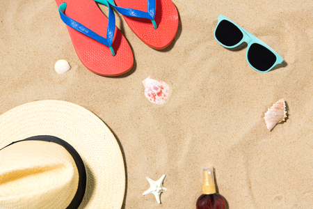 straw hat, flip flops and sunglasses on beach sand Stock Photo