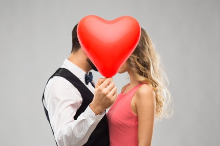 couple hiding behind red heart shaped balloon