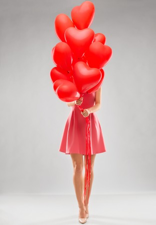 young woman with red heart shaped balloons