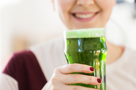 close up of woman with green beer in glass Stock Photo - 114867848