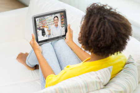 woman having video chat with pharmacist on tablet