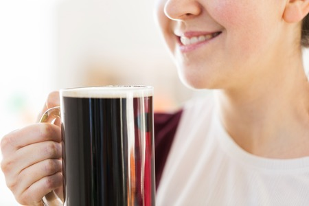 close up of smiling woman with dark beer in mug Stock Photo - 114868015
