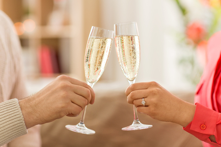 close up of couple clinking champagne glasses