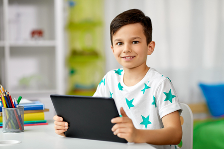 student boy with tablet pc and notebook at home
