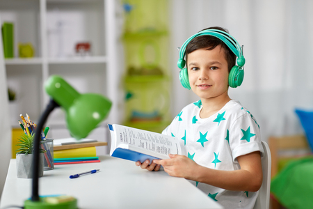boy in headphones with textbook learning at home