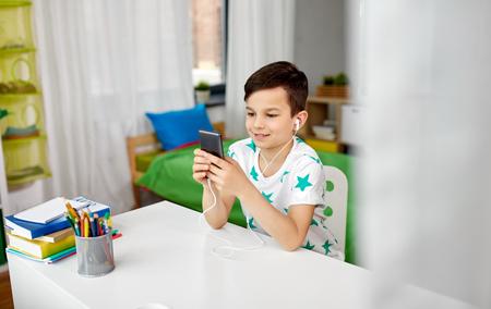 boy in earphones listening to music on smartphone