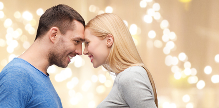 couple forehead to forehead over festive lights Stock Photo