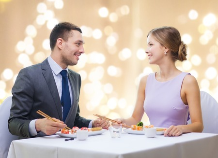 smiling couple eating sushi rolls at restaurant