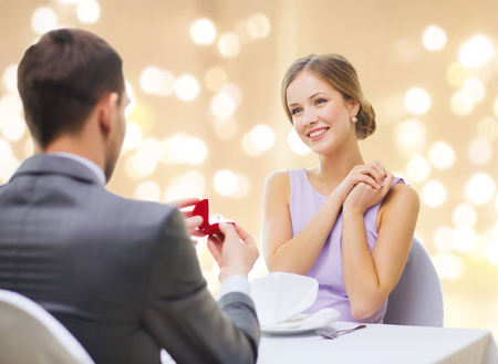 man giving woman engagement ring at restaurant