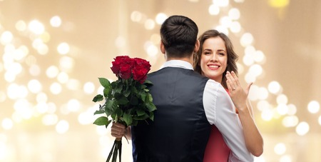woman with engagement ring and roses hugging man