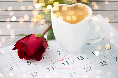 close up of calendar, heart, coffee and red rose