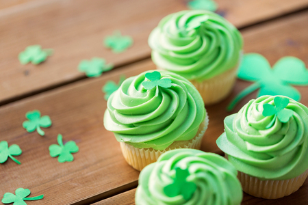 green cupcakes and shamrock on wooden table