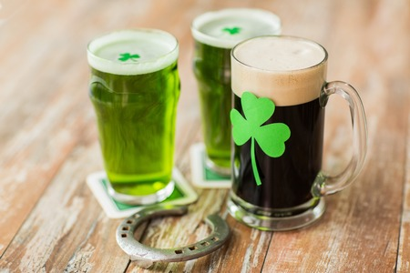 shamrock on glass of beer and horseshoe on table