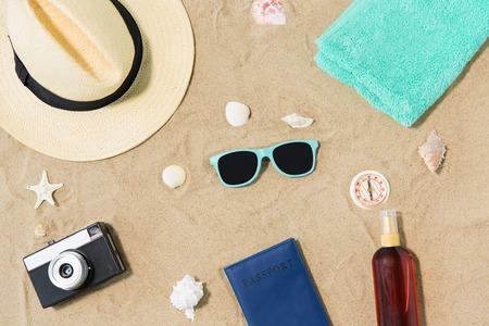 camera, passport, sunglasses and hat on beach sand Reklamní fotografie