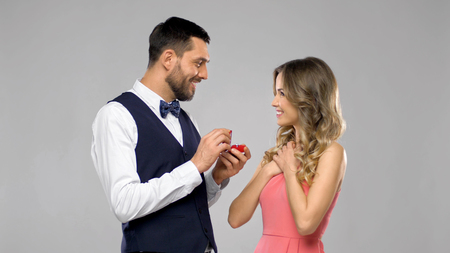 happy man giving engagement ring to woman