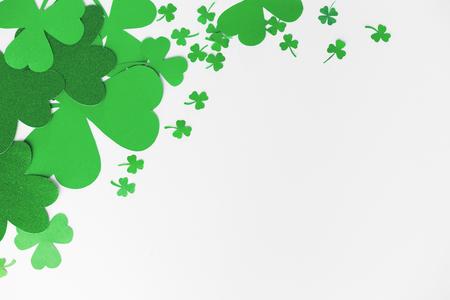 green paper shamrocks on white background