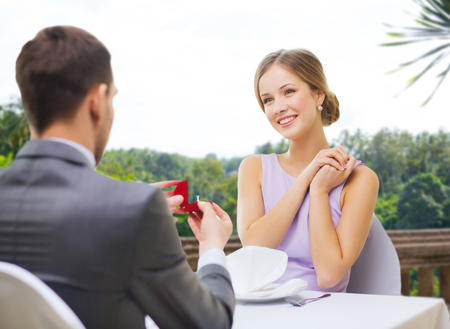 man giving woman engagement ring at restaurant