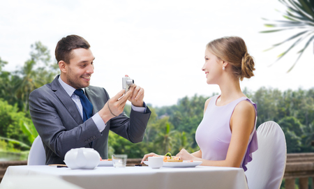man photographing woman by camera at restaurant