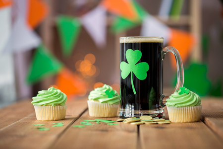 shamrock on glass of beer, green cupcake and coins