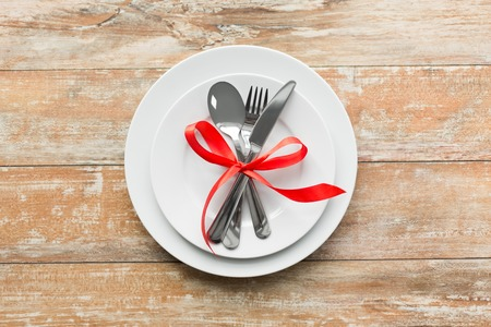 cutlery tied with red ribbon on set of plates Imagens
