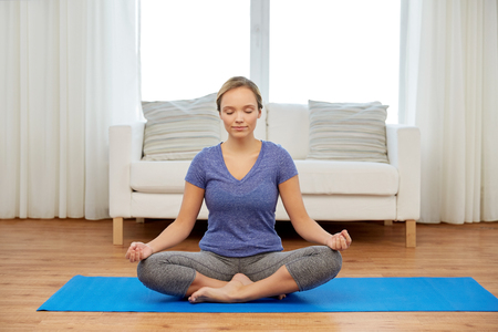 woman meditating in lotus pose at home