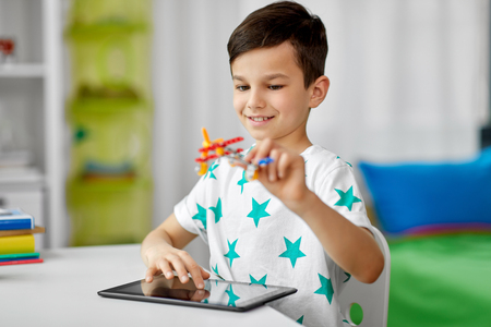 boy with tablet computer and toy airplane at home