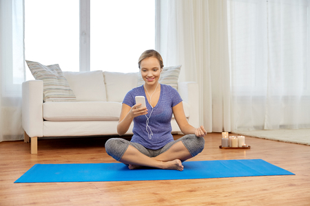 woman with music on smartphone doing yoga at home