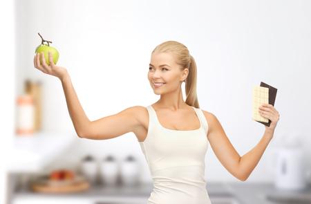 woman choosing green apple instead of chocolate 写真素材