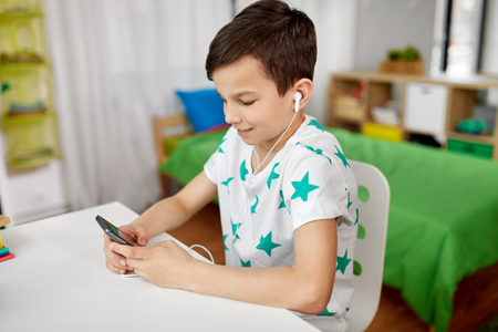 boy in earphones listening to music on smartphone