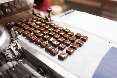 Caramelos de chocolate sobre cinta transportadora en confitería