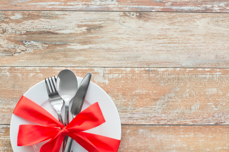 cutlery tied with red ribbon on set of plates Stock Photo