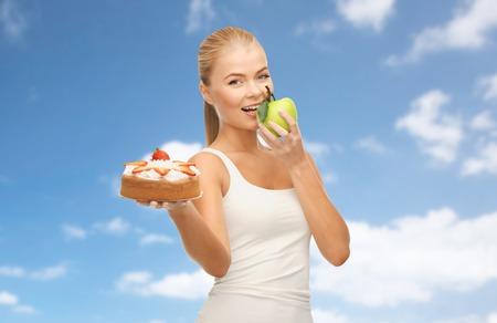 happy woman eating apple instead of cake 写真素材