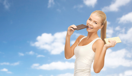 happy woman eating dark chocolate instead of white 写真素材